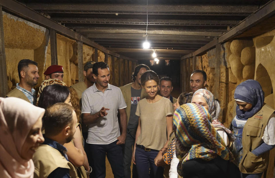 FILE - In this Aug. 16, 2018, file photo, released on the official Facebook page of the Syrian Presidency, Syrian President Bashar Assad, center left, and his wife Asma, center right, talk with Syrian artists during their visit to one of tunnels that were dug by rebels while they were under siege, in Jobar, near the Syrian capital Damascus, Syria. The unprecedented public crackdown on Syria's wealthiest businessman Rami Makhlouf,, a close cousin of Bashar Assad, comes as the embattled president seeks to consolidate power and rein in war profiteers. Syria is preparing for a new phase of economic hardship and U.S.-led sanctions that some say might be more difficult to weather than war. (Syrian Presidency Facebook Page via AP, File)