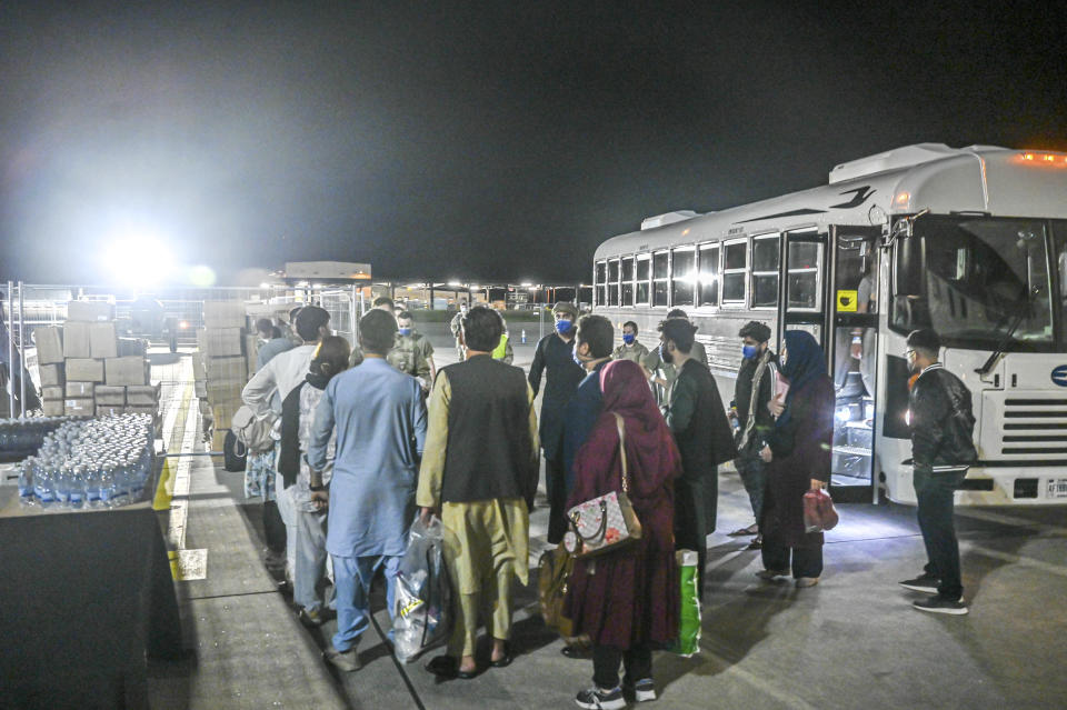 In this image provided by the U.S. Air Force, a group of Afghan evacuees depart a bus at Ramstein Air Base, Germany, Friday, Aug. 20, 2021. Ramstein Air Base is providing safe, temporary lodging for qualified evacuees from Afghanistan as part of Operation Allies Refuge during the next several weeks. (Senior Airman Jan K. Valle/U.S. Air Force via AP)