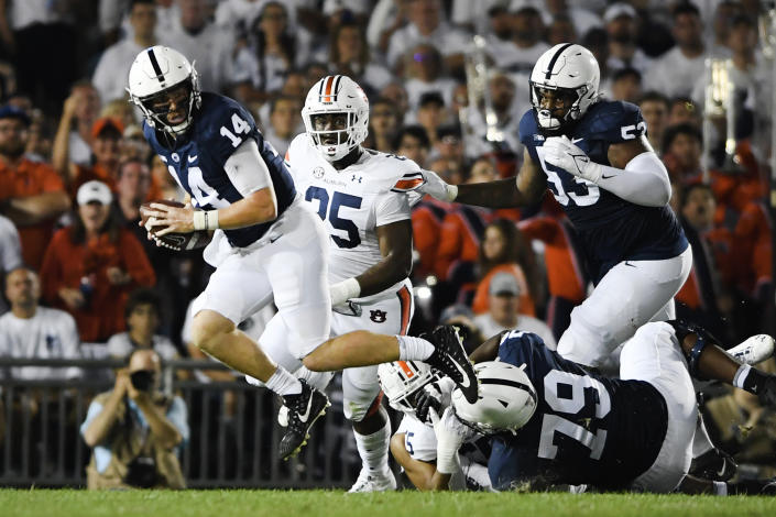Penn State quarterback Sean Clifford (14) scrambles away from Auburn defensive end Colby Wooden (25) during an NCAA college football game against Auburn in State College, Pa., on Saturday, Sept. 18, 2021. (AP Photo/Barry Reeger)