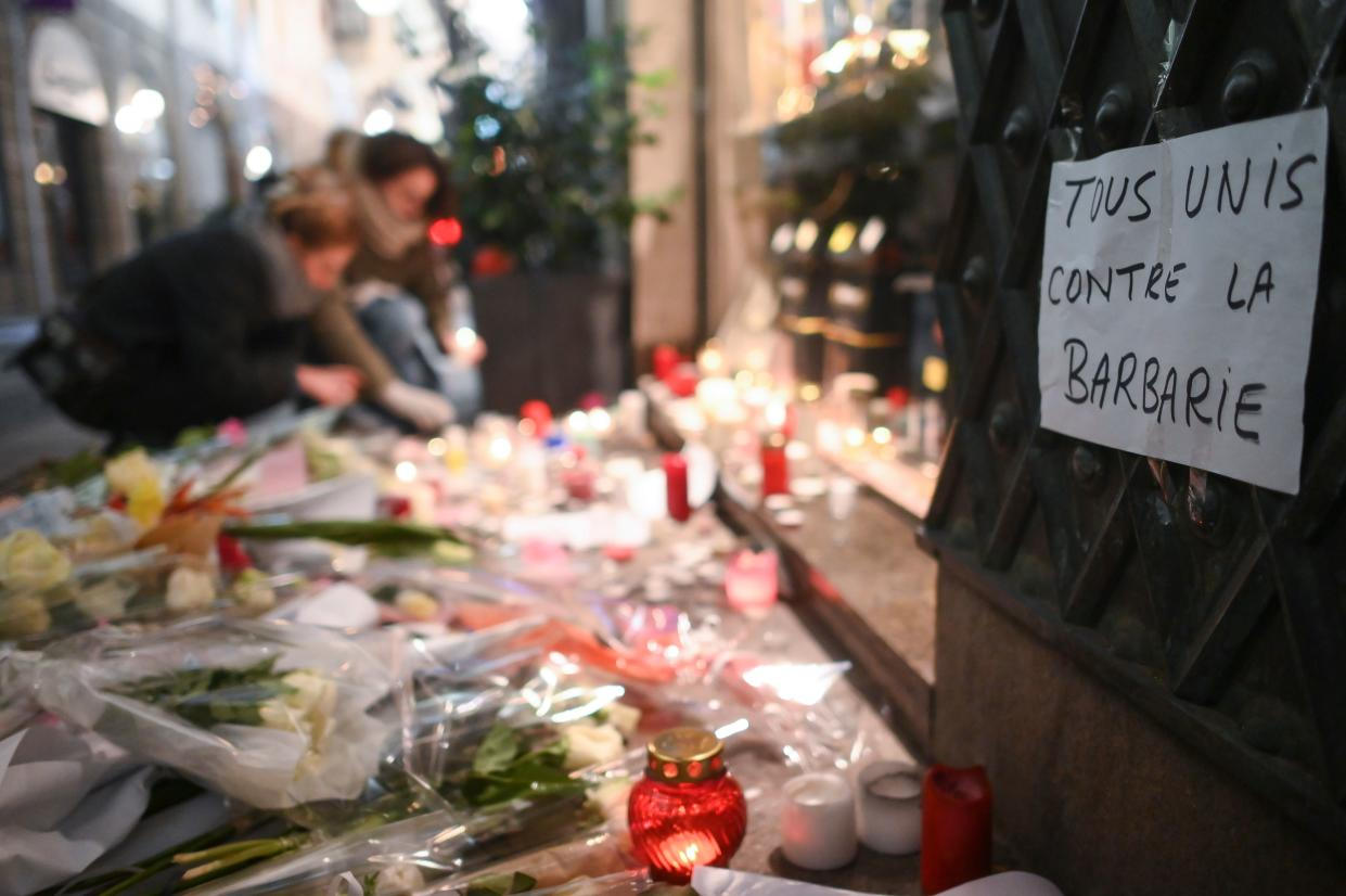 """A sheet of paper reading """"all together against barbarism"""" as people light candles on Dec. 13, 2018, in memory of the victims of the attack near the Christmas market of Strasbourg, in eastern France, on Dec.11, 2018. (Photo: Sebastien Bozon/AFP/Getty Images)"""