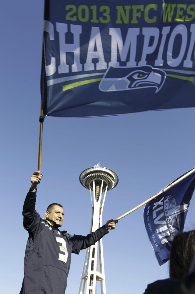 A Seattle Seahawks fan waves a flag with the Space Needle behind at a parade for the Super Bowl champions in Seattle on Wednesday, Feb. 5, 2014. The Seahawks beat the Denver Broncos 43-8 in the NFL Super Bowl XLVIII football game on Feb. 2, 2014. (AP Photo/John Froschauer)