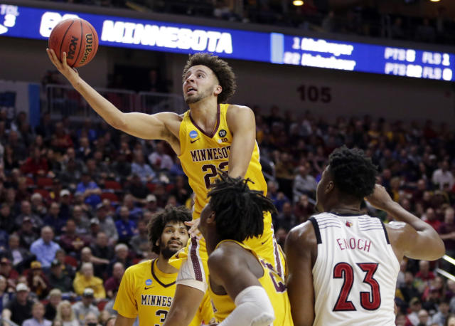 Minnesota's Gabe Kalscheur (22) goes for a layup as Louisville's Steven Enoch (23) watches during the second half of a first round men's college basketball game in the NCAA Tournament in Des Moines, Iowa, Thursday, March 21, 2019. (AP Photo/Nati Harnik)