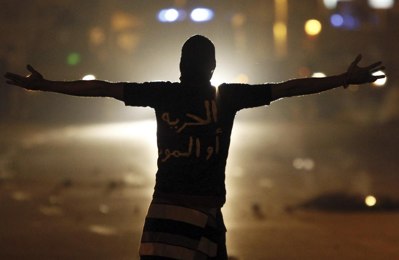 """<p>A protester passionately shouts slogans at riot police during clashes in front of the presidential palace in Cairo. The words on the shirt reads, """"Freedom or Death."""" (Reuters)</p>"""
