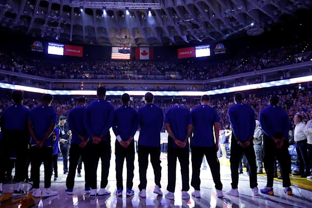 "Members of the <a class=""link rapid-noclick-resp"" href=""/nba/teams/gsw/"" data-ylk=""slk:Golden State Warriors"">Golden State Warriors</a> stand during the national anthem before their NBA pre-season game against the <a class=""link rapid-noclick-resp"" href=""/nba/teams/den/"" data-ylk=""slk:Denver Nuggets"">Denver Nuggets</a> at Oracle Arena in Oakland, California, U.S., September 30, 2017. REUTERS/Stephen Lam"