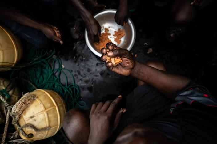 Gambian fishermen holding fistfuls of fishmeal. (Fábio Nascimento / The Outlaw Ocean Project)