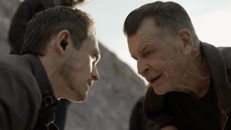 Two men in profile look at each other up close while on the ground
