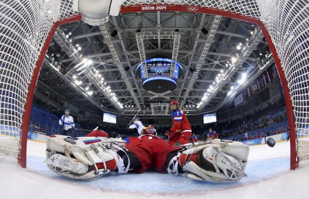 The puck flies into the net for Finland's second goal next to Russia's goalie Anna Prugova (bottom) during the first period of their women's ice hockey classification game at the Sochi 2014 Winter Olympic Games February 18, 2014.REUTERS/Martin Rose/Pool (RUSSIA - Tags: SPORT ICE HOCKEY OLYMPICS)