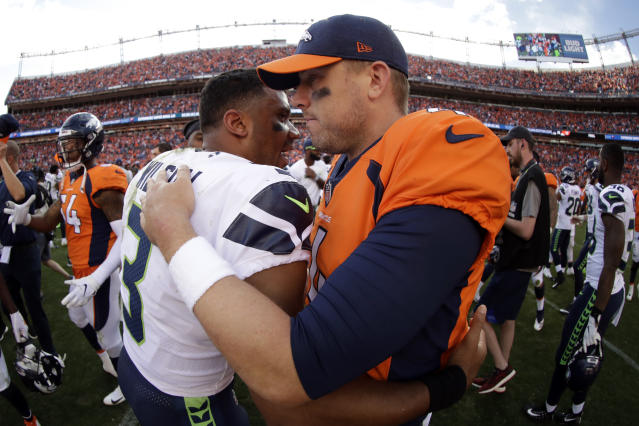 Denver Broncos quarterback Case Keenum, right, greets Seattle Seahawks quarterback Russell Wilson, left, after an NFL football game Sunday, Sept. 9, 2018, in Denver. The Broncos won 27-24. (AP Photo/Jack Dempsey)