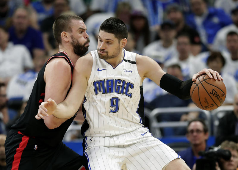 Orlando Magic's Nikola Vucevic (9) tries to get past Toronto Raptors' Marc Gasol during the first half in Game 3 of a first-round NBA basketball playoff series, Friday, April 19, 2019, in Orlando, Fla. (AP Photo/John Raoux)