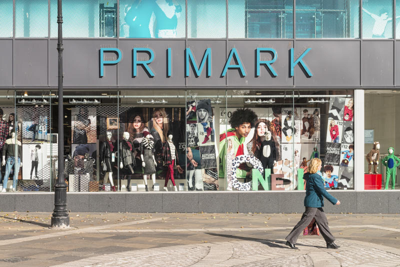 Dundee, UK - October 10, 2013: A woman walking past a window display for the Primark at the Overgate shopping centre in central Dundee.