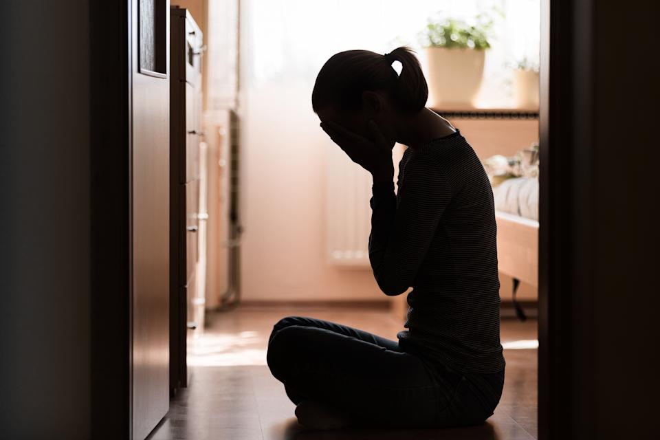 Sad young woman sitting on room floor crying with hand over face (Photo: kieferpix via Getty Images)
