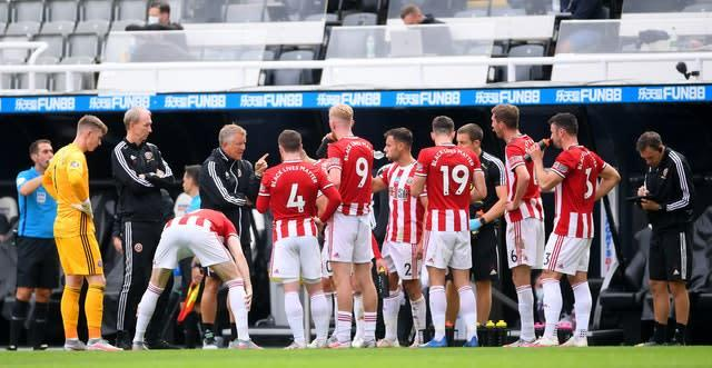 Chris Wilder talks to his players during a drinks break at St James' Park (Laurence Griffiths/NMC Pool/PA)
