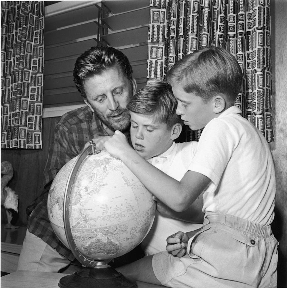 <p>Kirk gets hands on with his sons Michael and Joel as they explore a world globe together.</p>