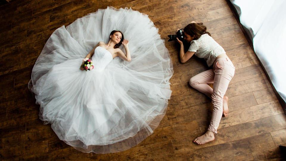 Young sexy woman photographer is taking pictures the bride in the studio.
