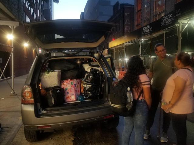 """<span class=""""s1"""">A childhood friend and fellow evacuee helps Jenyffer Ortiz pack her belongings into a car. (Photo: Kadia Tubman/Yahoo News)</span>"""