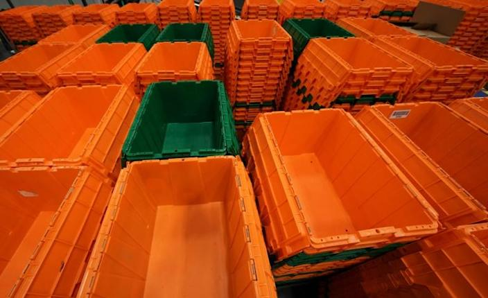 Orange and green plastic bins -- the company's signature colors -- zip along on conveyor belts overhead (AFP Photo/TIMOTHY A. CLARY)