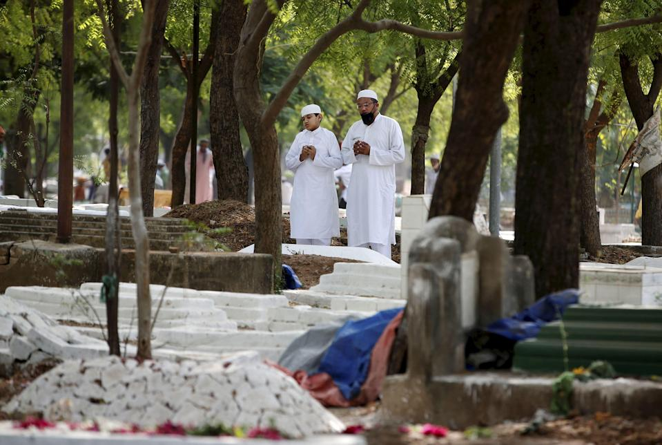 Muslims offer prayers next to the graves of their relatives on the occasion of Eid-ul-Fitr, at a graveyard in Ahmedabad, Friday, May 14, 2021.