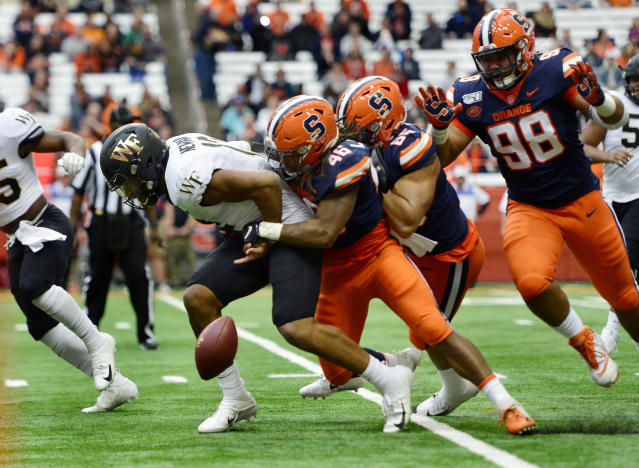 Syracuse linebacker Lakiem Williams (46) forces a fumble on Wake Forest quarterback Jamie Newman, left, during the first half of an NCAA college football game in Syracuse, N.Y., Saturday, Nov. 30, 2019. The fumble was recovered by Syracuse and would lead to a field goal for the Orangemen. (AP Photo/Adrian Kraus)