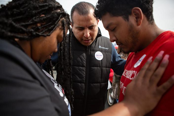 Omar Lugo, center, founder of Latinos for Trump in Alamance County, prays with supporters at a Trump rally in Elon, N.C.