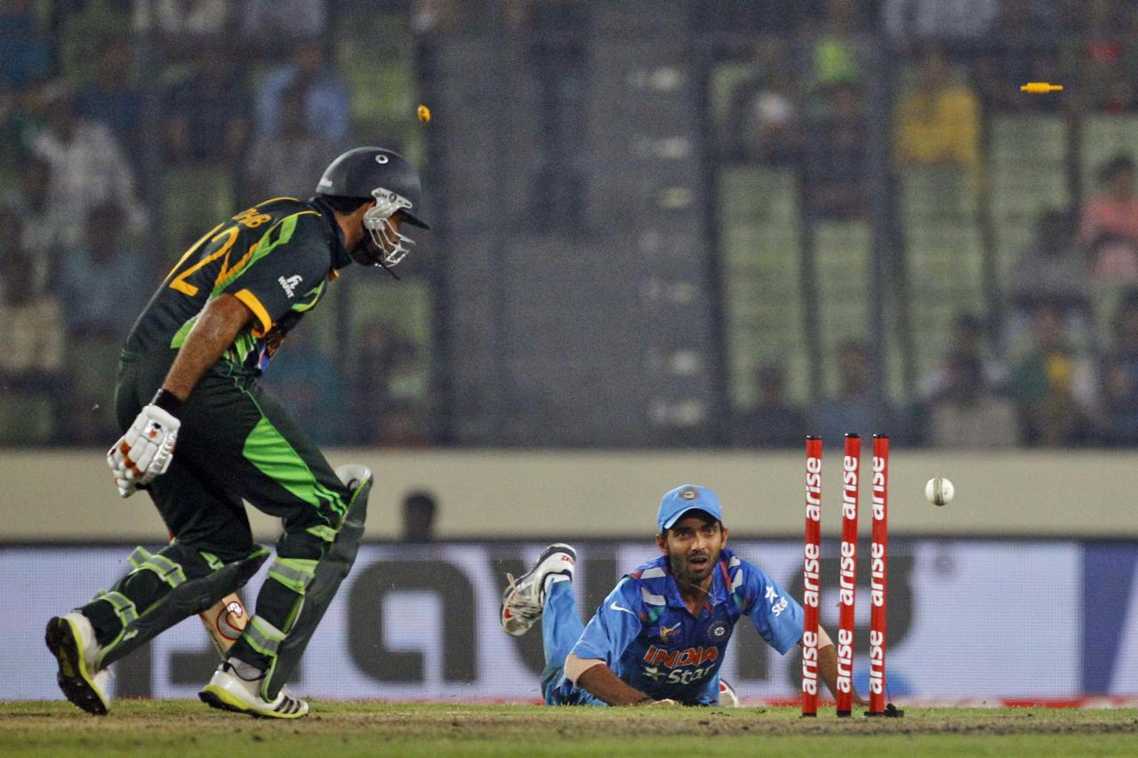 India's Ajinkya Rahane, left, unsuccessfully dislodges the bails to dismiss Pakistan's Sohaib Maqsood during the Asia Cup one-day international cricket tournament between them in Dhaka, Bangladesh, Sunday, March 2, 2014. Pakistan won by 1 wicket. (AP Photo/A.M. Ahad)