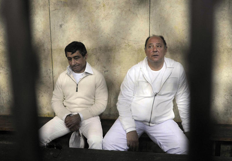 FILE - In this Thursday, Feb. 24, 2011 file photo, former Egyptian Tourism Minister Zuheir Garana, right, and steel tycoon and prominent ruling party leader Ahmed Ezz, left, wearing white prison uniforms, sit in a metal cage as they appear in the Cairo Criminal Court in Cairo, Egypt. An Egyptian court has convicted a Hosni Mubarak-era steel tycoon of profiteering and squandering public funds, and sentenced him to 37 years in prison. The court Wednesday found Ezz guilty of making illicit gains of $740 million in a number of illegal business deals involving his steel firm.(AP Photo, File)