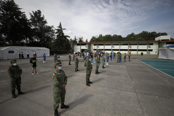 Military and civilian personnel follow social distancing protocols as they assemble outside after an earthquake, at a COVID-19 hospital in Military Camp 1, in Naucalpan, Mexico State, part of the Mexico City metropolitan area, Tuesday, June 23, 2020. The earthquake struck near the Huatulco resort in southern Mexico on Tuesday morning, swayed buildings in Mexico City and sent thousands fleeing into the streets. (AP Photo/Rebecca Blackwell)
