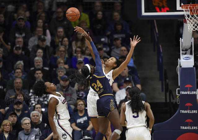Connecticut's Olivia Nelson-Ododa blocks a shot attempt from Notre Dame's Destinee Walker, left, as Connecticut's Christyn Williams, far left, and Crystal Dangerfield, right, defend in the first half of an NCAA college basketball game, Sunday, Dec. 8, 2019, in Storrs, Conn. (AP Photo/Jessica Hill)