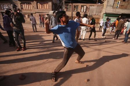 A Kashmiri boy throws a stone towards Indian security forces (not pictured) during clashes, after scrapping of the special constitutional status for Kashmir by the Indian government, in Srinagar