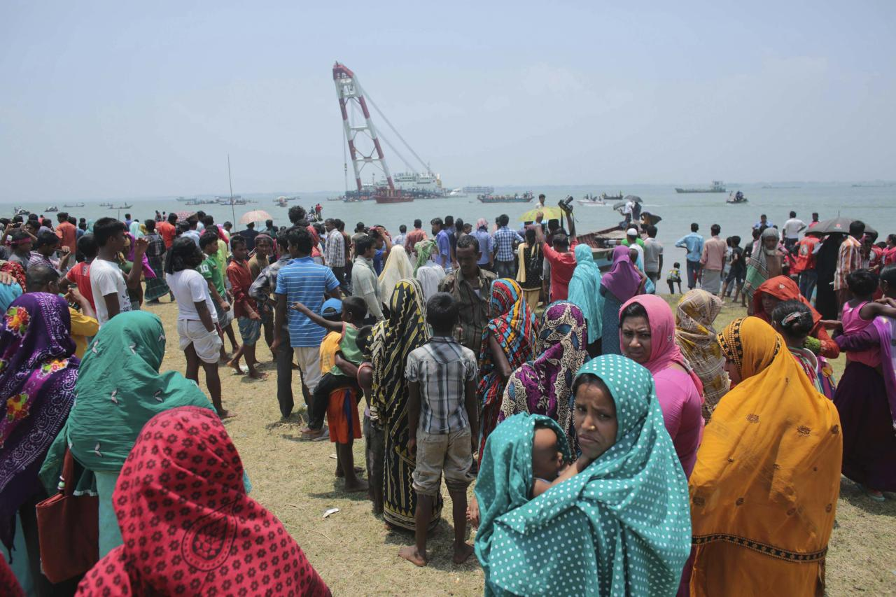 Relatives wait as they watch the rescue operation after the M.V. Miraj-4 ferry capsized, by the Meghna river at Rasulpur in Munshiganj district May 16, 2014. A Bangladeshi official said on Friday there was no chance of finding further survivors of the ferry that sank in a storm with about 200 people on board, the latest in a series of fatal ferry accidents to hit the poverty-stricken country. REUTERS/Andrew Biraj (BANGLADESH - Tags: DISASTER MARITIME)