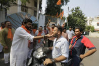 A Vishwa Hindu Parishad (VHP) supporter feeds sweets to a passerby in Ahmadabad, India, Saturday, Nov. 9, 2019. India's Supreme Court has ruled in favor of a Hindu temple on a disputed religious ground and ordered that alternative land be given to Muslims. The dispute over land ownership has been one of the country's most contentious issues. (AP Photo/Ajit Solanki)