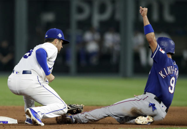Kansas City Royals second baseman Whit Merrifield, left, tags out Texas Rangers' Isiah Kiner-Falefa on an attempted steal during the seventh inning of a baseball game at Kauffman Stadium in Kansas City, Mo., Tuesday, June 19, 2018. (AP Photo/Orlin Wagner)