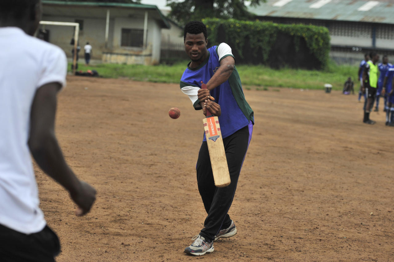 TO GO WITH AFP STORY BY FRAN BRANDY A man bats on November 15, 2012 in Freetown at  Kingtom Oval, Sierra Leone's only cricket oval. Packed with hard red dirt overlooked by a faded scoreboard, it is worlds away from the lush, carefully grassed grounds typically associated with the game. During the devastating 11-year conflict which left 120,000 dead and thousands maimed by rebels, the field, which belongs to an adjacent police station, became home to hundreds of refugees looking for safety. Cricket has a rich history in the west African nation, where it was introduced by the British in the late 19th century, and had a thriving club and schools league until war broke out in 1991.  AFP PHOTO / ISSOUF SANOGO        (Photo credit should read ISSOUF SANOGO/AFP/Getty Images)