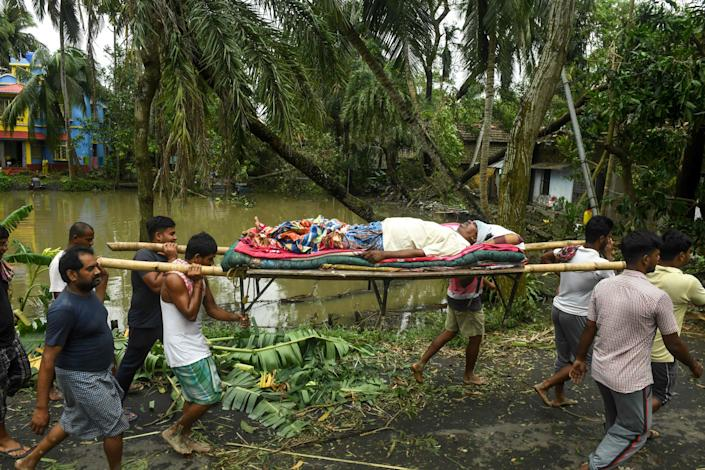 Image: Residents carry Tapas Pramanik (C), 41, after his leg got broken by a tree fall the night before, in search of an ambulance or vehicle to take him to the hospital, following the landfall of cyclone Amphan in Khejuri area of Midnapore, West Bengal, (Dibyangshu Sarkar / AFP - Getty Images)