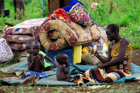 An elderly woman displaced by fighting in South Sudan rests by her belongings in Lamwo after fleeing fighting in Pajok town across the border in northern Uganda