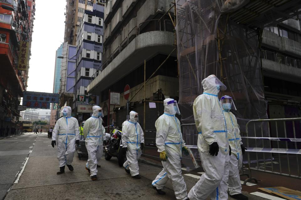 Cleaners wearing protective suits, gather in the Yau Ma Tei area, in Hong Kong, Saturday, Jan. 23, 2021. Thousands of Hong Kong residents were locked down Saturday in an unprecedented move to contain a worsening outbreak in the city, authorities said. (AP Photo/Vincent Yu)