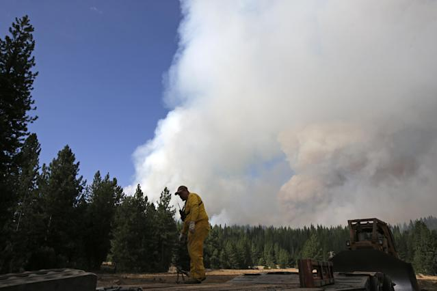 A contractor prepares to load a bulldozer onto a trailer as a smoke plume from the Rim Fire rises near Yosemite National Park, Calif., on Sunday, Aug. 25, 2013. With winds gusting and flames jumping from treetop to treetop, hundreds of firefighters have been deployed to protect this and other communities in the path of the Rim Fire raging north of Yosemite National Park. (AP Photo/Jae C. Hong)