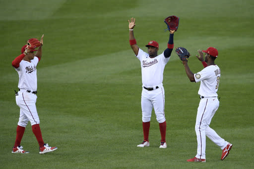 Washington Nationals' Victor Robles, center, Juan Soto, left, and Michael A. Taylor, right, celebrate after the first baseball game of a doubleheader against the Miami Marlins, Saturday, Aug. 22, 2020, in Washington. (AP Photo/Nick Wass)