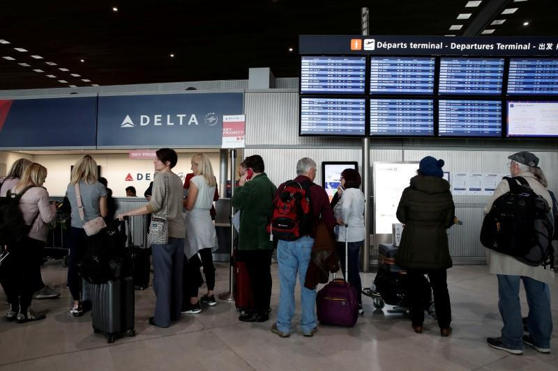 FILE PHOTO: People line up at the Delta Air Lines ticketing desk inside Terminal 2E at Paris Charles de Gaulle airport