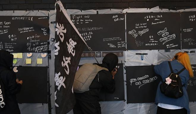 The demonstrators signed their names on a memorial board that bore the names of 26 people who, they believed, had died during police operations or killed themselves over the ongoing social unrest. Photo: Winson Wong