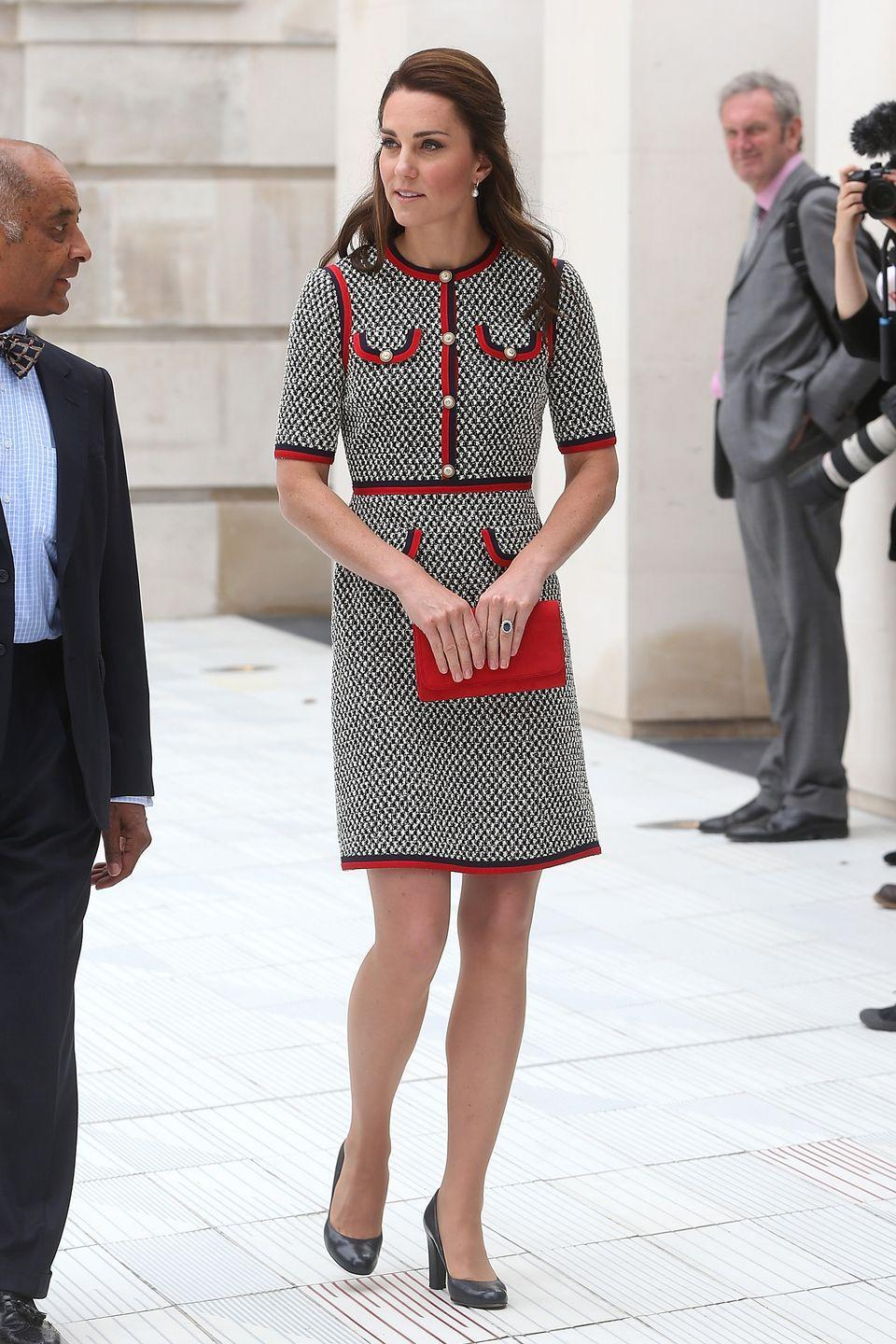 <p>In a Gucci tweed dress, red clutch and black heels at the Victoria and Albert Museum in London. </p>