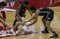 Wisconsin's Brad Davison goes after a loose ball with Minnesota's Jamal Mashburn Jr. (4) and Eric Curry during the second half of an NCAA college basketball game Thursday, Dec. 31, 2020, in Madison, Wis. (AP Photo/Morry Gash)