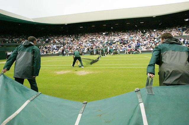 The net is pulled down, as ground staff pull rain covers onto the Centre Court, as rain interupts play on the seventh day of the All England Lawn Tennis Championships, at Wimbledon, Monday, June 30, 2003.(AP Photo/Dave Caulkin)