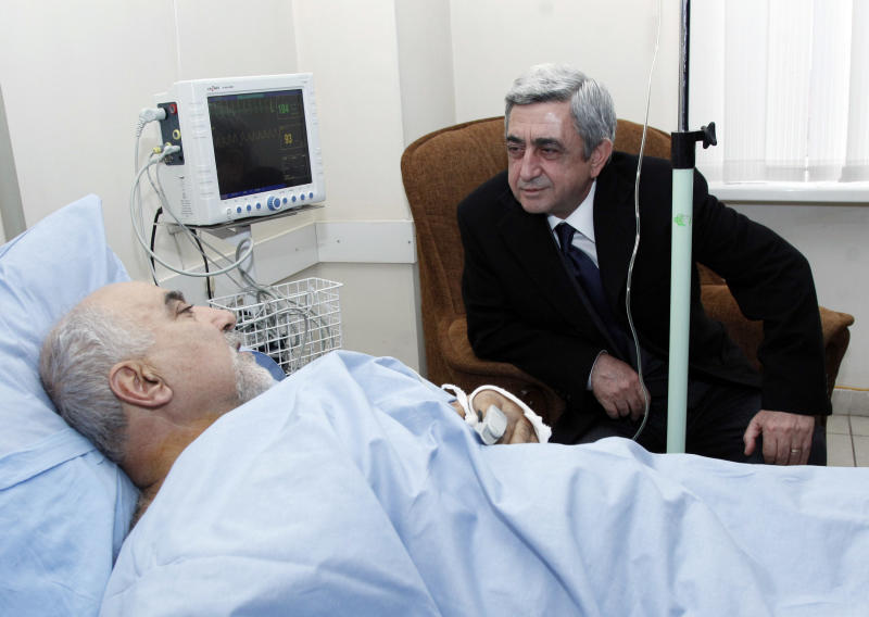 Armenian President Serge Sarkisian visits Paruir Airikian, a candidate for the Armenian presidency, who was shot and wounded by unidentified assailant outside his home, in a hospital ward after a surgery in Yerevan, Armenia, Friday, Feb. 1, 2013. A midnight shooting attack on a presidential candidate threw Armenia's election into disarray Friday, raising the prospect that the vote could be postponed. Paruir Airikian, 63, was shot and wounded by an unidentified assailant outside his home in Yerevan, the Armenian capital, just before midnight. He was recuperating Friday after surgery. He is one of eight candidates in the Feb. 18 race in this landlocked former Soviet republic and wasn't expected to get more than 1 percent of the vote. But the attack might force authorities to delay the election, a move that could help opponents of President Serge Sarkisian, who was expected to easily win a second five-year term. (AP Photo/Tigran Mehrabyan, PanARMENIAN)