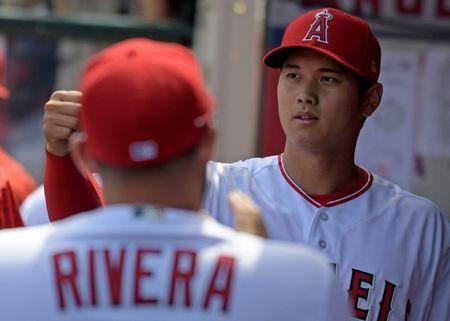 Apr 8, 2018; Anaheim, CA, USA; Los Angeles Angels starting pitcher Shohei Ohtani (17) is greeted by teammates in the dugout against the Oakland Athletics during a MLB baseball game at Angel Stadium of Anaheim. Kirby Lee-USA TODAY Sports