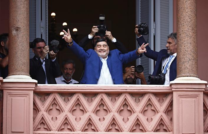 Diego Maradona flashes victory signs to fans after meeting with Argentine President Alberto Fernandez on Dec. 26, 2019.