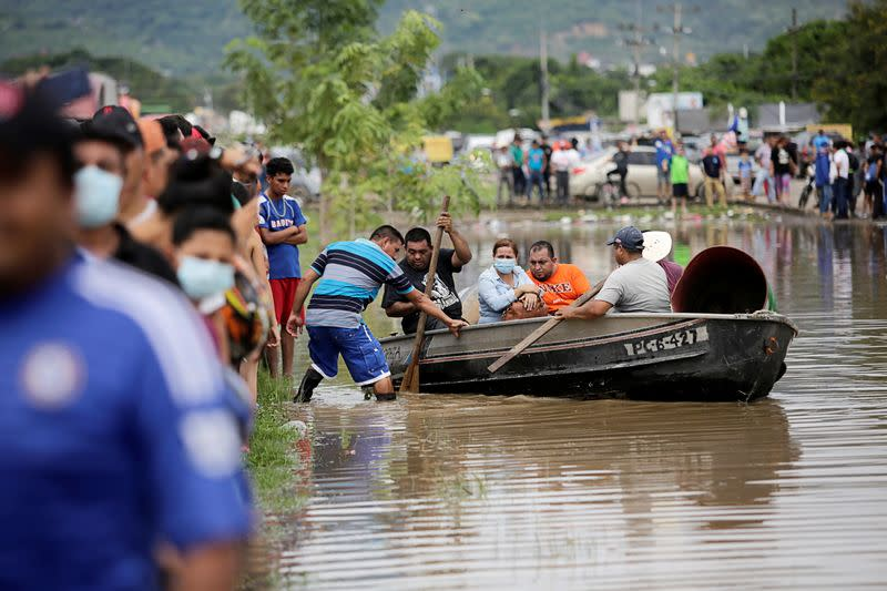 People board a boat to get to their flooded house during the passage of Storm Eta, in Pimienta
