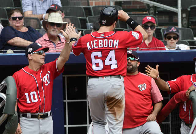 Washington Nationals' Spencer Kieboom (64) enters the dugout after scoring on a line drive to right field by Adam Eaton during the sixth inning of a baseball game Saturday, Sept. 15, 2018, in Atlanta. (AP Photo/John Amis)