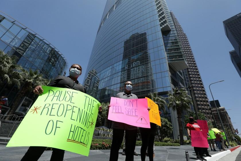 LOS ANGELES, CA - JULY 08: Hotel workers protest for their safety in front of the InterContinental Los Angeles Downtown on Wednesday, July 8, 2020 in Los Angeles, CA. A spokesperson said a survey of hospitality workers found that the lack of safety measures such as having hand sanitizer, gloves and companies' lack of enforcing social distancing rules, were risking the workers' health. The spokesperson added that given the choice between saving the economy or saving their families, they'll save their families. (Myung J. Chun / Los Angeles Times)