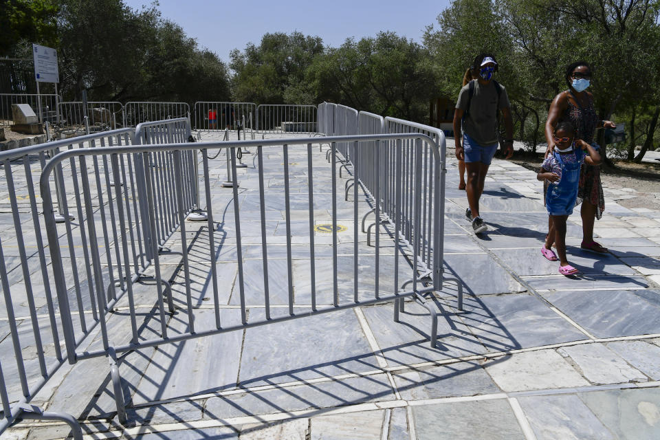 Tourists walk by the closed entrance of the ancient Acropolis, in Athens Greece, Tuesday, Aug. 3, 2021. Authorities in Greece have closed the Acropolis and other ancient sites during afternoon hours as a heatwave scorching the eastern Mediterranean continued to worsen. Temperatures reached 42 C (107.6 F) in parts of the Greek capital, as the extreme weather fueled deadly wildfires in Turkey and blazes across the region. (AP Photo/Michael Varaklas)
