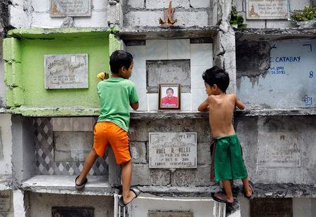 Boys look at the tomb of Michael Almeda, who was among those allegedly killed by the Bonnet Gang, in more than 60 drug-related vigilante killings in the town of Pateros, Metro Manila